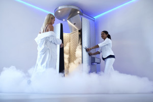 Female taking cryotherapy treatment with woman standing at the capsule door.